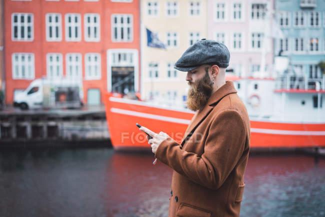 Vista lateral do elegante homem que navega smartphone sobre barco ancorado no cais da cidade em segundo plano — Fotografia de Stock