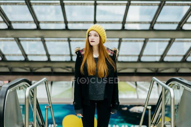 Hübsche junge rothaarige Frau steht im Einkaufszentrum und schaut weg. — Stockfoto
