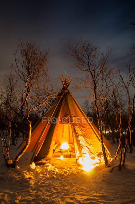 Tente avec feu de joie à l'intérieur à la forêt givrée couverte de neige la nuit . — Photo de stock