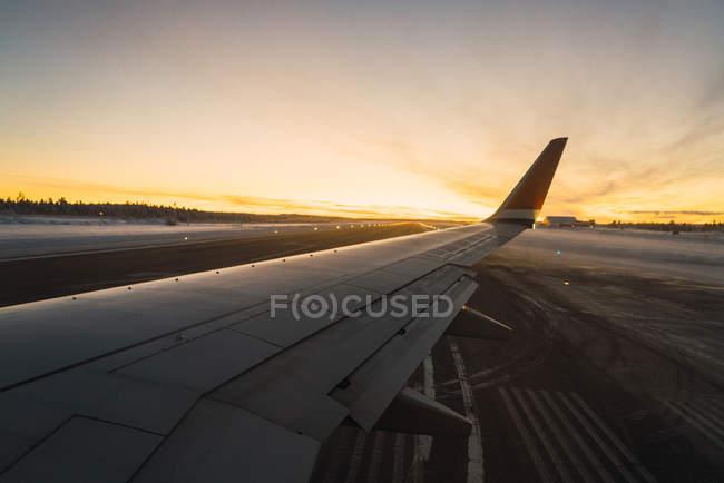 Vista para asa de avião no aeroporto em luzes de pôr do sol . — Fotografia de Stock
