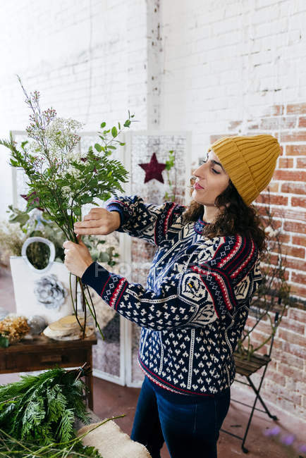 Side view of woman in knitted sweater arranging flowers — Stock Photo