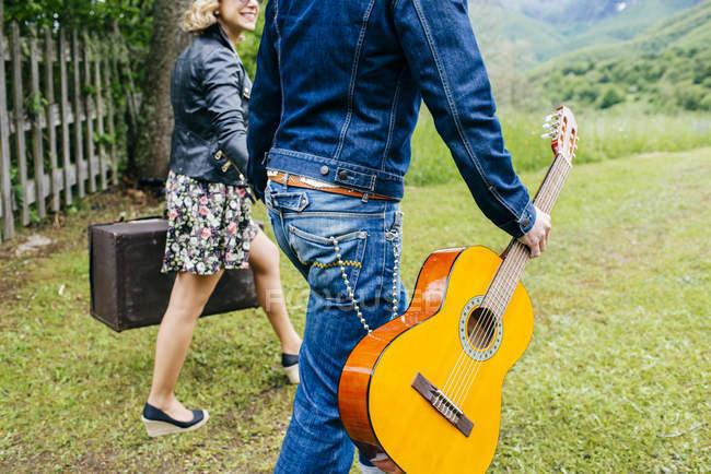Erntepaar Händchen haltend und mit Gitarre auf grünem Rasen. — Stockfoto