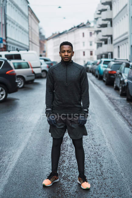 Full-length portrait of man in warm sportive clothes posing on street and looking at camera — Stock Photo