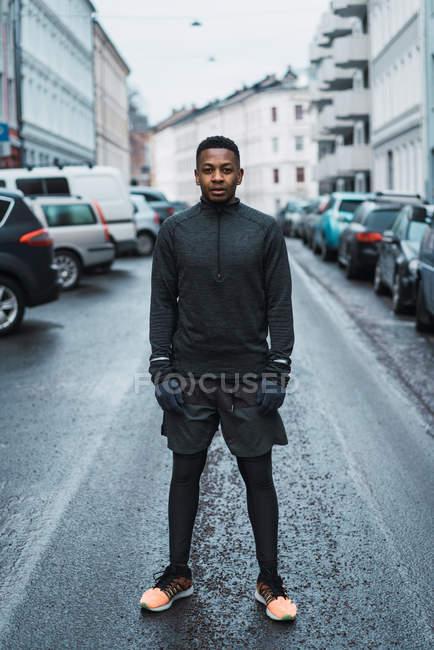 Porträt des Mannes in warme sportliche Kleidung posiert auf Straße und Blick in die Kamera — Stockfoto