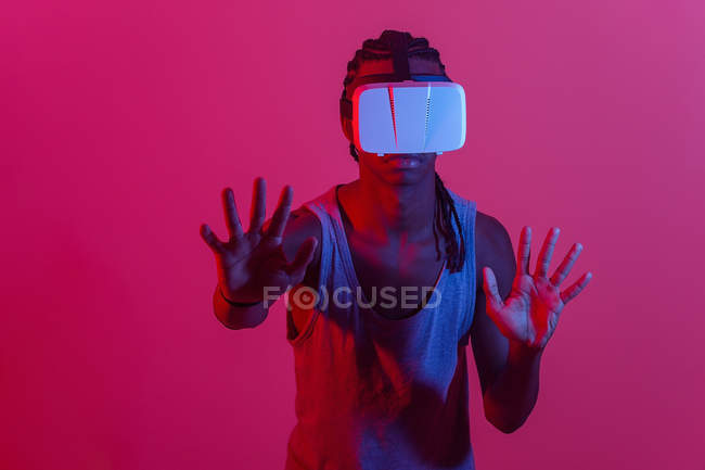 Young black man using VR headset and outstretching palms in front — Stock Photo