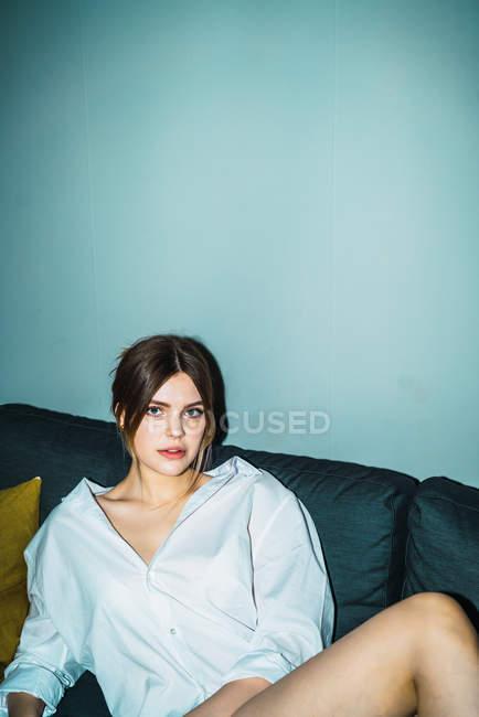 Attractive woman posing on sofa at looking at camera — Stock Photo