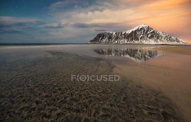 Vista del paisaje al lago congelado y las montañas cubiertas de nieve en día de invierno. - foto de stock