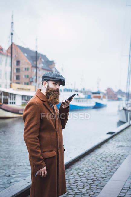 Seitenansicht eines bärtigen Mannes in Mantel und Mütze per Sprachsuche auf Smartphone am Fluss in der Stadt — Stockfoto