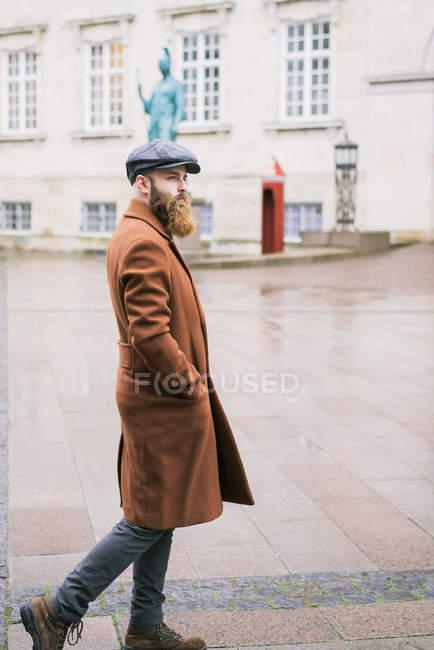 Vista laterale dell'uomo barbuto che indossa cappotto e cappuccio in posa sulla scena della strada — Foto stock