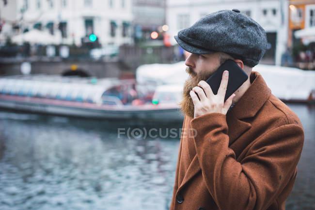 Vue latérale de l'homme barbu en chapeau parlant sur smartphone à la rivière en ville — Photo de stock