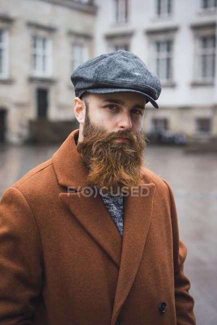 Vista frontal do homem barbudo vestindo casaco vintage e boné posando na cena da cidade e olhando para a câmera — Fotografia de Stock