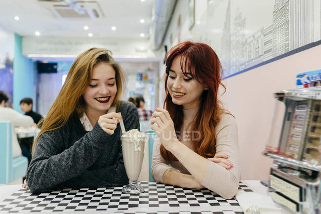 Two pretty young women sitting in cafe and having cocktail together. — Stock Photo