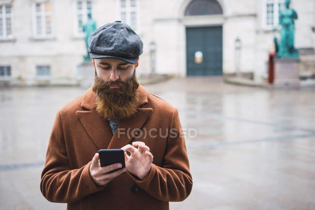 Uomo barbuto in cappotto e cappello utilizzando smartphone sulla strada  della città — Foto stock d96391723e77