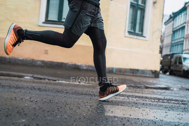 Crop male legs running at street scene — Stock Photo