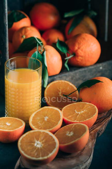Stillleben mit frischen Orangen und Glas mit Orangensaft — Stockfoto