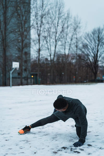 Side view of athletic man squatting on snowy ground and outstretching leg to warming up muscles — Stock Photo