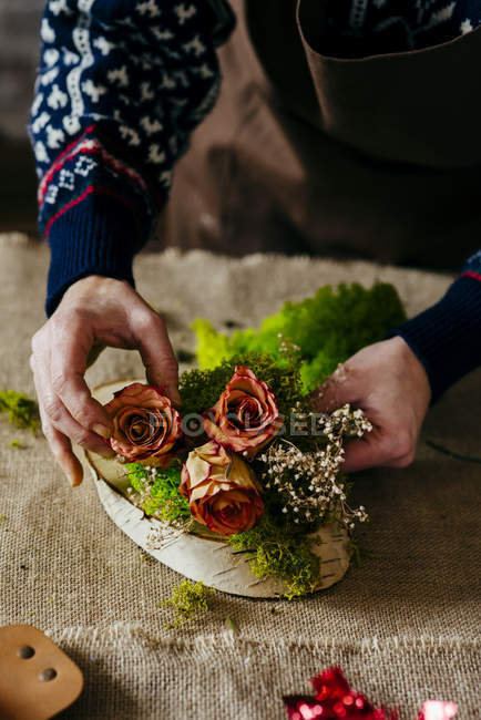 Crop female hands in knitted sweater making floral composition on table — Stock Photo