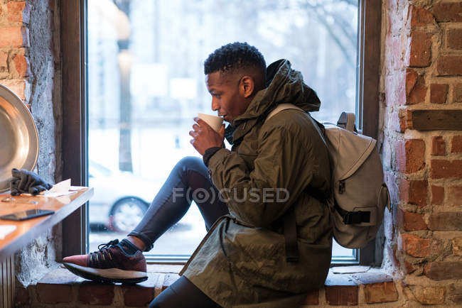 Side view of tourist man sitting on window sill in cafe and drinking hot beverage — Stock Photo