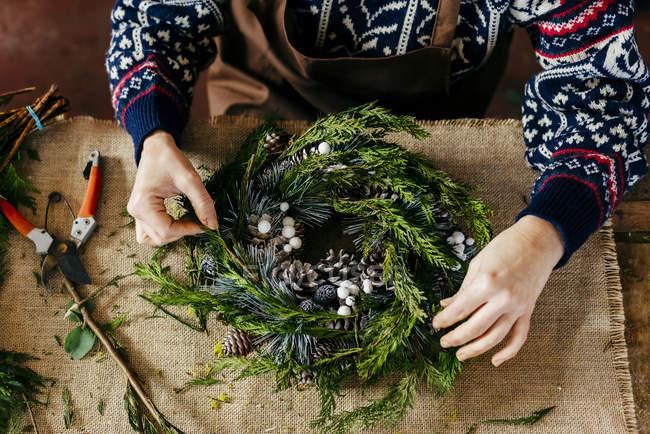 Crop floristas mãos fazendo grinalda de Natal em saquear à mesa — Fotografia de Stock
