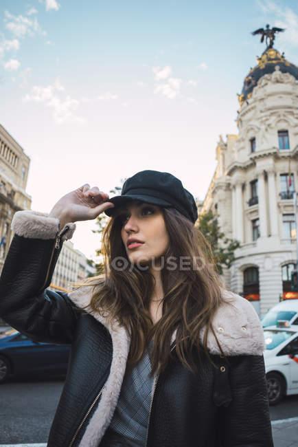 Портрет брюнетка жінки cap постановки на вулиці і хтось дивитися вбік, у — стокове фото