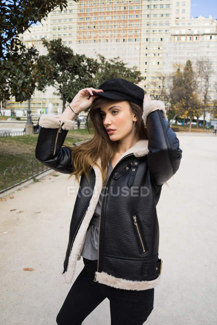 Porträt einer stylischen brünetten Frau, die sich im Park eine Mütze aufsetzt — Stockfoto