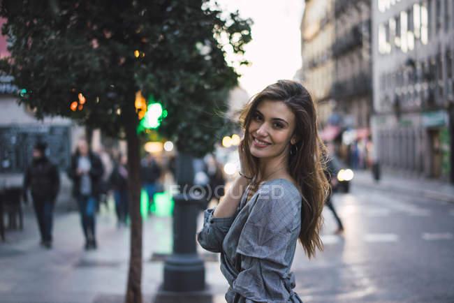 Vista laterale di una donna bruna sorridente sulla strada urbana — Foto stock