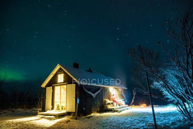 View to illuminated wooden chaletin winter — Stock Photo