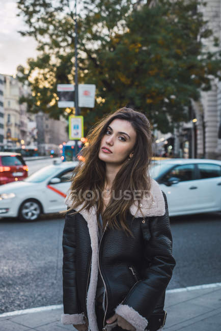 Stylish woman posing on street and looking at camera — Stock Photo