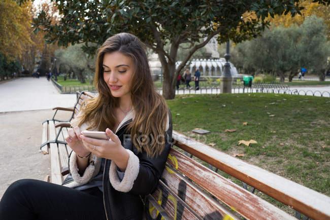 Портрет женщины со смартфоном на скамейке в парке — стоковое фото