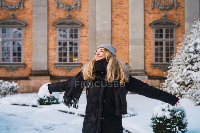 Portrait of blonde woman posing widely outstretched arms in winter town — Stock Photo