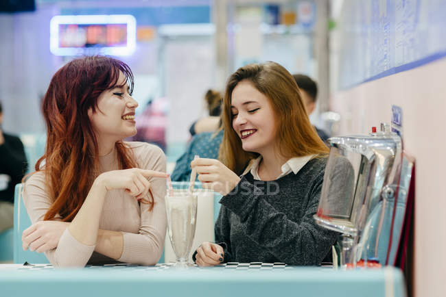 Side view of two smiling women having cocktails at cafe — Stock Photo