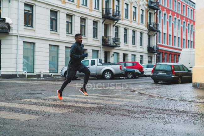Vista laterale dell'uomo atletico che corre sulla strada della città — Foto stock