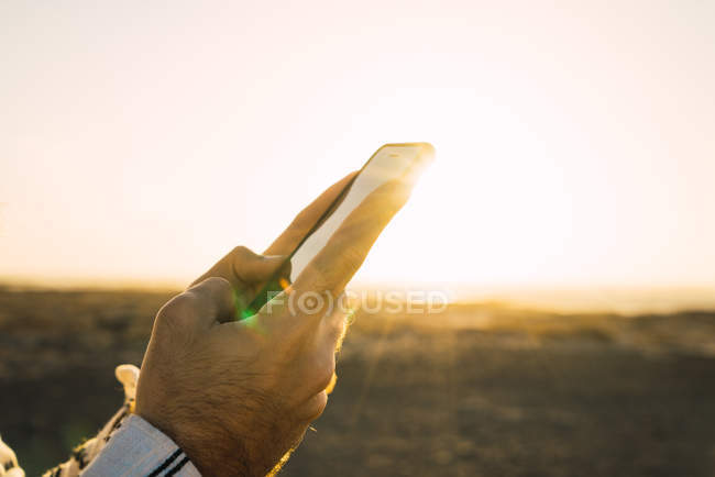 Crop vale hands browsing smartphone on background of sunlit valley — Stock Photo