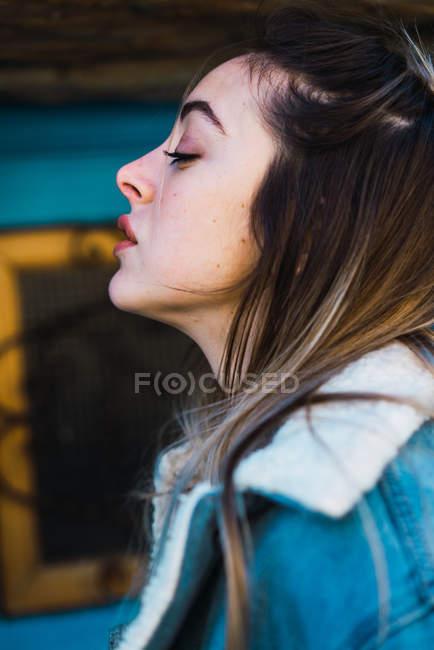 Вид сбоку кокетливой женщины, позирующей на улице — стоковое фото