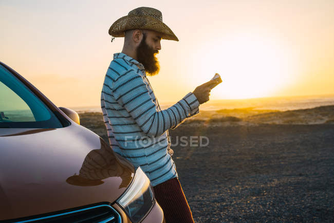 Side view of confident traveler leaning on car and reading map at shoreline — Stock Photo