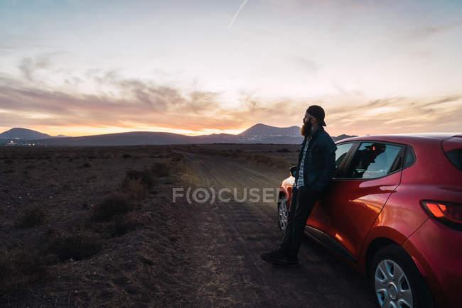 Турист опирается на крышу автомобиля и наслаждается пейзажем в сумерках — стоковое фото
