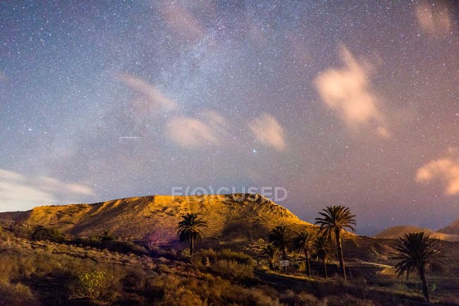 Panoramic view to hills and starry cloudy sky at night in countryside — Stock Photo