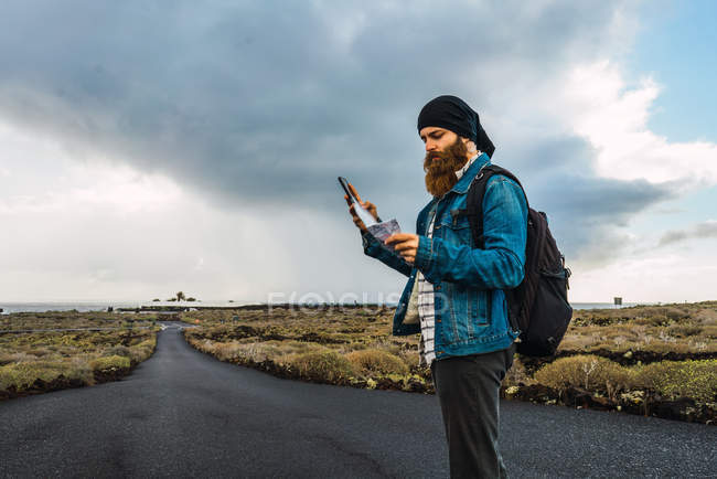 Side view of tourist man with map and smartphone — Stock Photo