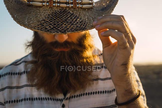 Hombre barbudo ocultando los ojos con sombrero contra la luz del sol - foto de stock