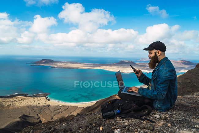 Vista laterale dell'uomo seduto sulla scogliera costiera con laptop in ginocchio e smartphone di navigazione — Foto stock