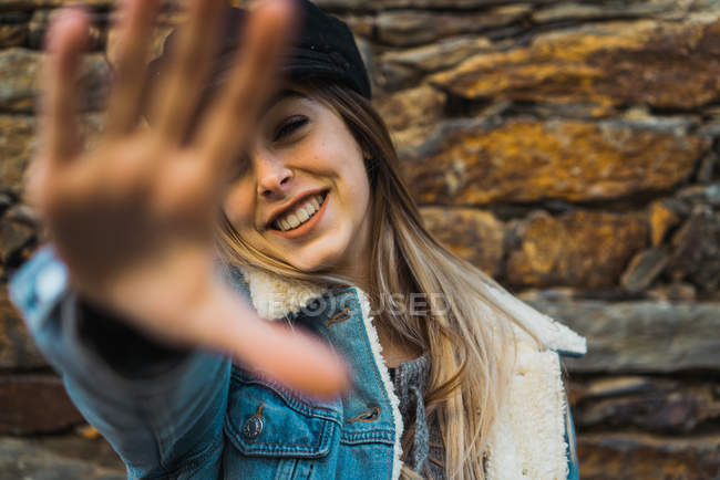 Portrait of laughing stylish girl outstretching hand towards camera — Stock Photo