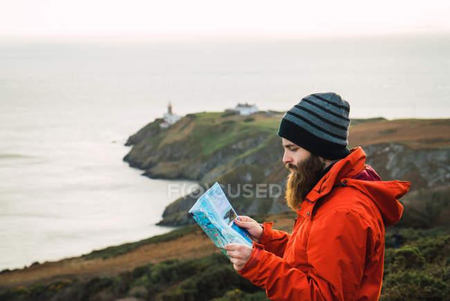Vista lateral del hombre barbudo posando con mapa sobre colinas costeras - foto de stock