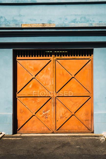 Außenaufnahme des Gebäudes blauen Fassade mit orange Metalltoren im Sonnenlicht. — Stockfoto