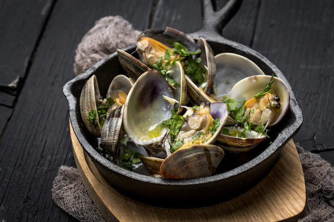 Still life of clam stew with white wine sauce served in rural pan — Stock Photo