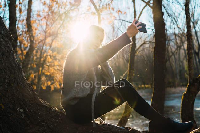 Вид збоку жінка, сидячи на стовбур дерева і беручи selfie з смартфон в Осінній Парк. — стокове фото