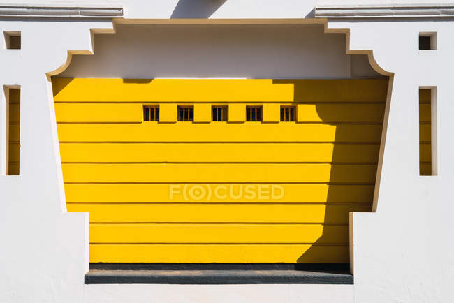 Exterior shot of white ornamental facade with yellow paneling in bright sunlight. — Stock Photo