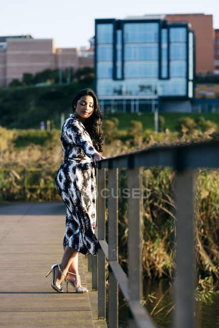 Vista lateral da mulher em belo vestido posando na ponte com os olhos fechados no parque da cidade — Fotografia de Stock