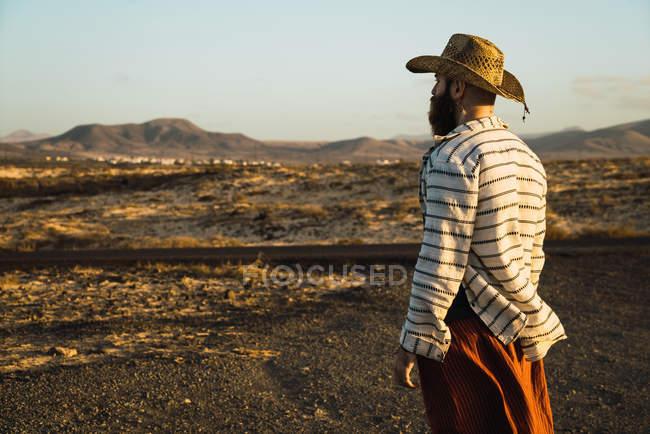 Vista lateral del hombre barbudo en sombrero contra la luz solar - foto de stock