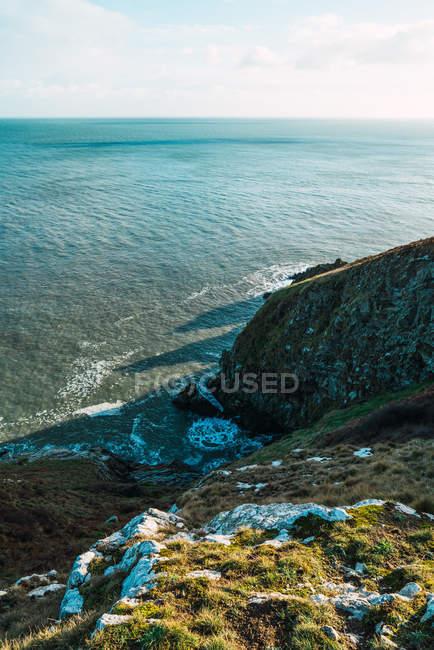 Низкий угол зрения для спокойный океан и прибрежные холмы, покрытые зеленой травы. — стоковое фото