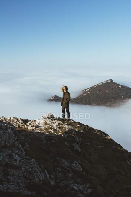 Viajante em pé na borda rochosa com fundo de pico de montanha em nuvens. — Fotografia de Stock